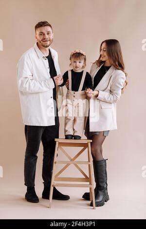 Ritratto di una giovane famiglia felice, con una piccola adorabile figlia. Genitori che tengono le mani di un bambino e la abbracciano. Bambino che sta in piedi su una scala di legno con