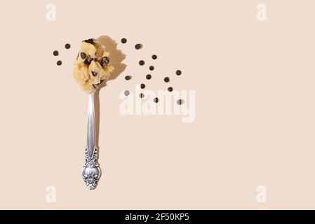 Impasto di biscotti commestibili in cucchiaio con gocce di cioccolato su sfondo giallo alla luce del sole, primo piano. Foto Stock
