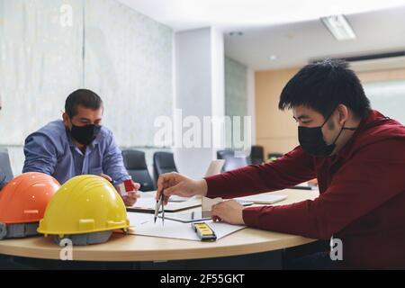 Team di architetti fiduciosi che lavorano insieme in un ufficio. Discutono del nuovo progetto di avvio sulla scrivania. Architetto discutere con ingegnere su pro