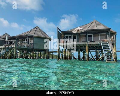 Villa d'acqua in legno con Oceano Turchese alle Maldive. Bella vista di Bungalows Overwater con Laccadive Sea in Maldivian Resort Komandoo.