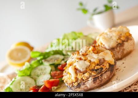 Cucina mediterranea. Funghi farciti con formaggio, insalata, pomodoro, cetriolo, limone.