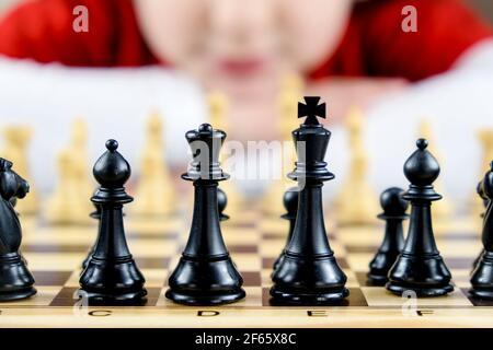 Primo piano di alcuni pezzi scacchi neri con il volto di una ragazza fuori fuoco sullo sfondo. Concetto di giocare a scacchi a casa, hobby a casa