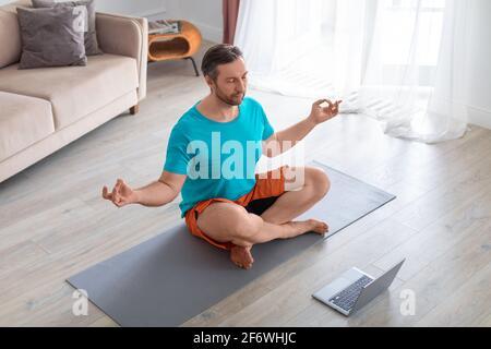 Uomo di mezza età che prende una lezione di yoga online. Sta meditando seduto sul pavimento di fronte a un monitor portatile. Foto Stock