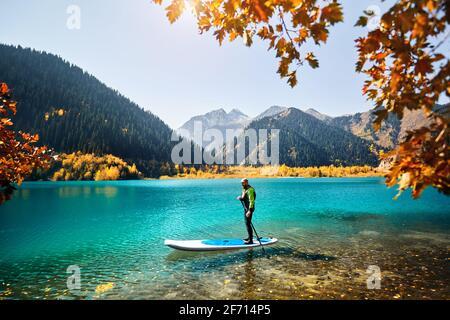 Uomo che galleggia su una tavola SUP presso il lago di montagna vicino alla foresta gialla in autunno. Avventura a stand up paddle boarding. Foto Stock