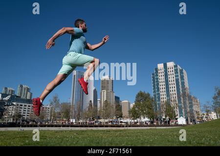 I piedi dei corridori dell'atleta corrono nel parco cittadino. Concetto di jogging all'aperto. Uomo che corre per l'esercizio su sfondo Città. Foto Stock