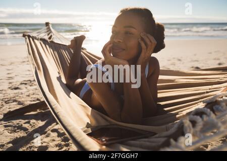 Donna afro-americana felice sdraiata in amaca sulla spiaggia guardando avanti Foto Stock