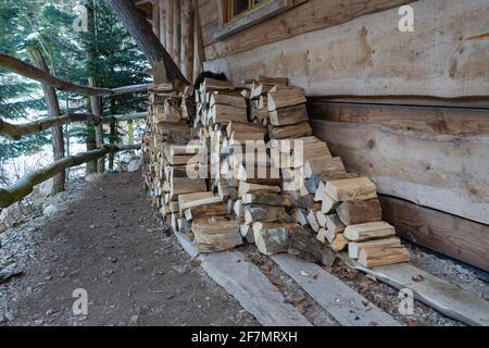 Mucchio di piccoli tronchi di fronte ad un cottage. Foto Stock