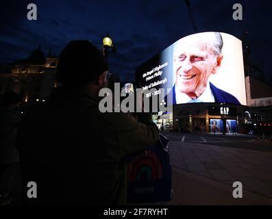 Un uomo usa il suo telefono cellulare per fotografare un tributo al Duca di Edimburgo, che sarà mostrato per 24 ore, in mostra al Piccadilly Lights nel centro di Londra, dopo l'annuncio della sua morte all'età di 99 anni. Data immagine: Venerdì 9 aprile 2021.