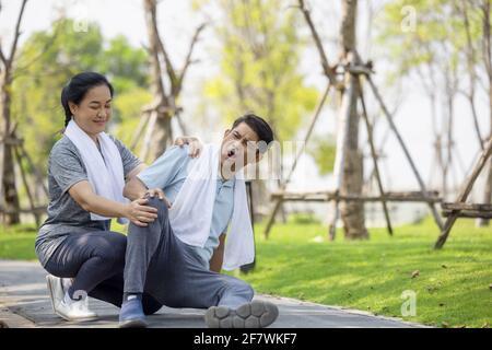 L'anziano asiatico o l'incidente dell'uomo anziano che cade sul pavimento nel parco durante l'esercizio in esecuzione hanno dolore al ginocchio.