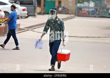 Dhaka, Dhaka, Bangladesh. 10 Apr 2021. Aprile, 10, 2021 UNA medica indossa uno scudo facciale per trasportare una scatola campione di COVID-19 Credit: Harun-or-Rashid/ZUMA Wire/Alamy Live News