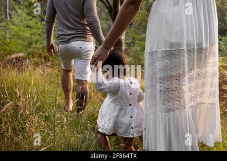 Giovane famiglia che cammina attraverso le praterie forestali.