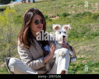 Giovane donna seduta su una roccia in un campo, in posa per una foto con il suo cucciolo bianco schnauzer.