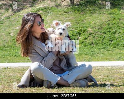 Giovane donna seduta a terra nel campo, trascorrendo del tempo con il suo cucciolo di schnauzer bianco.