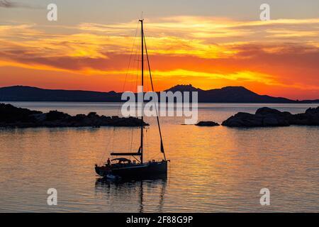 Godendo di un Golden, Tramonto: Yacht ormeggiato sulle acque calme della Sardegna attraverso un tranquillo Mediterraneo alle isole di la Madallena e Caprera Foto Stock
