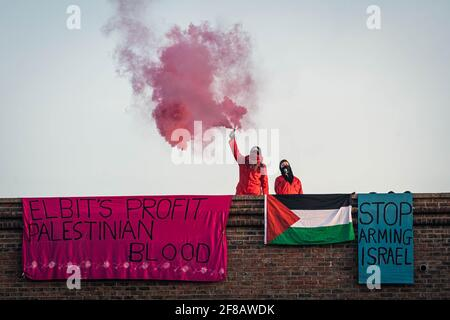 """Bristol, Regno Unito. 13 Apr 2021. Gli attivisti Palestine Action occupano il tetto del quartier generale di Elbit a Bristol nelle prime ore di mercoledì mattina. Le bandiere appendono dal tetto leggere """"il profitto di Elbit sangue palestinese"""" e """"smettere di armare Israele"""". Aztec West Business Park a Bristol, Regno Unito. Credit: Vladimir Morozov/akxmedia. Credit: Vladimir Morozov/Alamy Live News"""