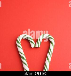 Caramelle dure a forma di cuore bianco e verde a strisce natalizie sul dorso rosso. Stile di posa piatto. Foto Stock