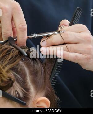 Le mani del parrucchiere tengono le forbici e tagliano una ciocca di capelli al cliente