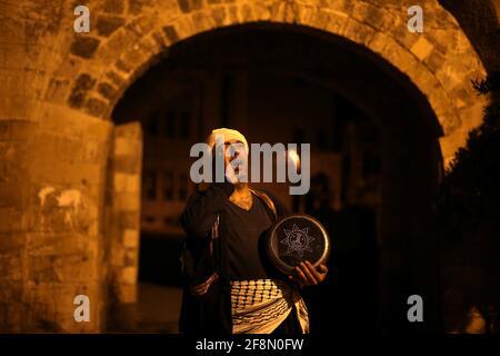 Un Mesaharati palestinese tiene un tamburo mentre chiede di svegliare i musulmani per avere il pasto prima dell'alba prima che comincino il loro digiuno di lunga giornata, durante il mese santo del Ramadan, in mezzo all'epidemia di coronavirus (COVID-19), a Khan Young nella striscia di Gaza meridionale 15 aprile 2021. REUTERS/Ibraheem Abu Mustafa