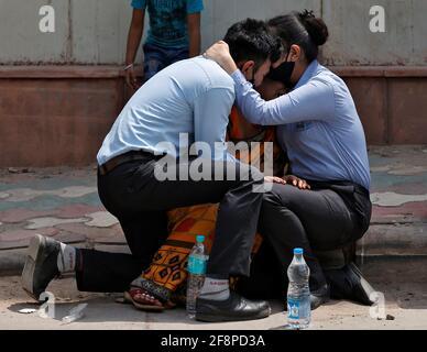 Una donna è consolata dai suoi figli dopo che suo marito è morto a causa della malattia del coronavirus (COVID-19) al di fuori di un mortuario di un ospedale COVID-19 a Nuova Delhi, India, 15 aprile 2021. REUTERS/Danese Siddiqui