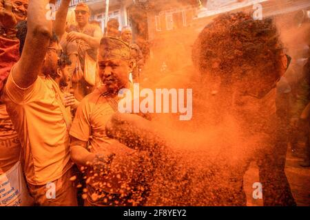 Bhaktapur, Nepal. 15 Aprile 2021. I devoti coperti di polvere di vermiglio celebrano il festival della polvere di 'Indoor Jatra'. I rivelatori portarono carri degli dei e delle dea indù e si gettarono vermilioni di polvere l'uno sull'altro come parte delle celebrazioni che iniziarono il nuovo anno nepalese. Credit: SOPA Images Limited/Alamy Live News