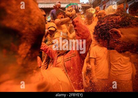 Bhaktapur, Nepal. 15 Aprile 2021. I popoli della comunità newari suonano strumenti tradizionali mentre gettano polvere di vermiglio (coperto) l'uno verso l'altro durante il festival indoor Jatra. I rivelatori portarono carri degli dei e delle dea indù e si gettarono vermilioni di polvere l'uno sull'altro come parte delle celebrazioni che iniziarono il nuovo anno nepalese. Credit: SOPA Images Limited/Alamy Live News