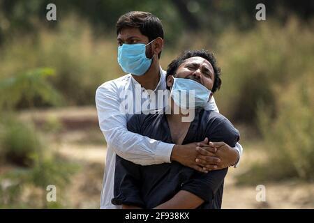 Un uomo è consolato dal suo parente come vede il corpo di suo padre, che è morto dalla malattia del coronavirus (COVID-19), prima della sua sepoltura in un cimitero a Nuova Delhi, India, 16 aprile 2021. REUTERS/Danese Siddiqui