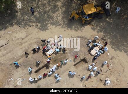La gente seppellisce i corpi delle vittime che sono morte a causa della malattia del coronavirus (COVID-19), in un cimitero a Nuova Delhi, India, 16 aprile 2021. Foto scattata con un drone. REUTERS/Danese Siddiqui