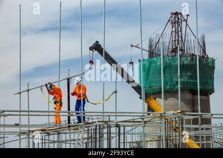 Atyrau/Kazakhstan - Maggio 21 2012: Modernizzazione degli impianti di raffineria petrolifera. Arrampicatori industriali sul montaggio di ponteggi. Costruzione del concre di rinforzo