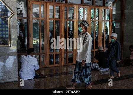 Makassar, Sulawesi del Sud, Indonesia. 16 Apr 2021. I musulmani camminano nella moschea al Markaz al Islami a Makassar per attendere le preghiere del venerdì nella congregazione. Le preghiere alla moschea nel mese di Ramadan sono effettuate con protocolli di salute, indossando maschere, e mantenendo la distanza. Credit: Herwin Bahar/ZUMA Wire/Alamy Live News