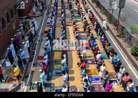 Dhaka, Bangladesh. 16 Apr 2021. I Musulmani eseguono la preghiera Jumma per strada senza mantenere alcuna distanza sociale il primo venerdì del mese santo del Ramadan, mentre le autorità del Bangladesh hanno imposto una stretta chiusura per combattere la diffusione del Covid-19 coronavirus Credit: SOPA Images Limited/Alamy Live News Foto Stock