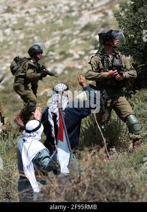 Nablus, Mideast. 16 Apr 2021. Un manifestante palestinese si scontra con i soldati israeliani e i membri della polizia di frontiera israeliana durante una protesta contro l'espansione degli insediamenti ebraici nel villaggio di Beit Dajan, ad est di Nablus, in Cisgiordania, il 16 aprile 2021. Credit: Aiyman Nobani/Xinhua/Alamy Live News