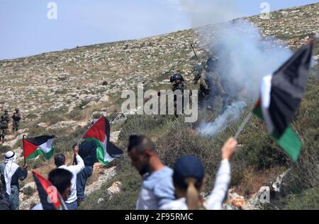 Nablus, Mideast. 16 Apr 2021. Un soldato israeliano spara un barattolo di gas lacrimogeno ai manifestanti palestinesi durante una protesta contro l'espansione degli insediamenti ebraici nel villaggio di Beit Dajan, a est di Nablus, in Cisgiordania, il 16 aprile 2021. Credit: Aiyman Nobani/Xinhua/Alamy Live News