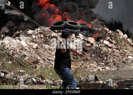 Nablus. 16 Apr 2021. Un manifestante palestinese usa una scagliata per gettare pietre contro i soldati israeliani durante gli scontri dopo una protesta contro l'espansione degli insediamenti ebraici nel villaggio di Kufr Qadoom vicino alla città di Nablus, sulla Cisgiordania, il 16 aprile 2021. Credit: Nidal Eshtayeh/Xinhua/Alamy Live News
