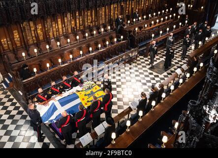 La regina Elisabetta II guarda come i portacolori portano la bara del duca di Edimburgo durante i suoi funerali alla St George's Chapel, Castello di Windsor, Berkshire. Data immagine: Sabato 17 aprile 2021.