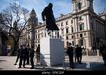 """Gli agenti di polizia si trovano accanto a una statua di Winston Churchill durante una protesta """"Kill the Bill"""" contro la polizia, il crimine, le sentenze e i tribunali Bill in Parliament Square, Londra. Data immagine: Sabato 17 aprile 2021."""