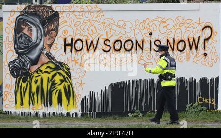 Un Garda passa davanti a un nuovo murale al Grand Canal Docks di Dublino dell'artista CHELS (Chelsea Jacobs), riflettendo l'incerto futuro dei bambini a causa delle restrizioni di Covid-19. Data immagine: Domenica 18 aprile 2021.