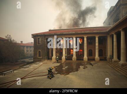 I vigili del fuoco combattono le fiamme mentre la biblioteca dell'Università di Città del Capo brucia dopo che un fuoco di funghi è scoppiato sulle pendici di Table Mountain a Città del Capo, Sudafrica, 18 aprile 2021. REUTERS/Mike Hutchings