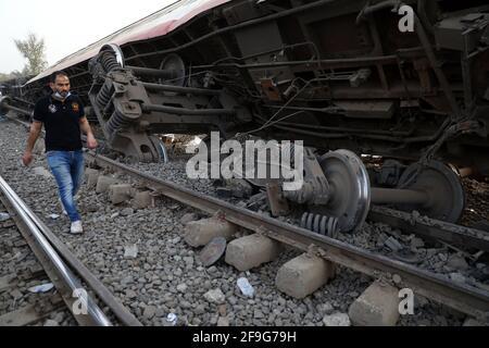 Toukh, Egitto. 18 Apr 2021. Un uomo cammina attraverso un treno deragliato nella città Delta di Toukh, Egitto, il 18 aprile 2021. Almeno 97 persone sono state ferite in un deragliamento ferroviario la domenica nella città del Delta di Toukh, a nord della capitale egiziana il Cairo, ha detto il Ministero della Salute egiziano. Credit: Ahmed Gomaa/Xinhua/Alamy Live News