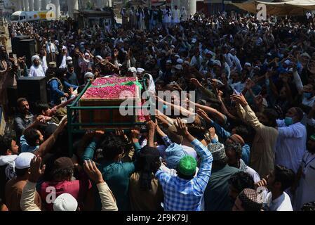 Lahore, Pakistan. 19 Apr 2021. I sostenitori del partito Tehreek-e-Labbaik Pakistan (TLP) portano la bara e gridano slogan durante la preghiera funeraria del loro collega di un compagno ucciso nello scontro domenicale con le forze di sicurezza, Una protesta dopo che il loro capo è stato arrestato a seguito del suo appello per l'espulsione dell'ambasciatore francese a Lahore. (Foto di Rana Sajid Hussain/Pacific Press) Credit: Pacific Press Media Production Corp./Alamy Live News Foto Stock