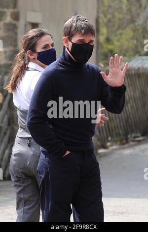 L'attore Tom Cruise ondeggia agli onlookers mentre cammina verso il set del suo ultimo progetto, che sta filmando ai sidi della stazione ferroviaria nel villaggio di Levisham nei Moors di North York. Data immagine: Martedì 20 aprile 2021. Foto Stock