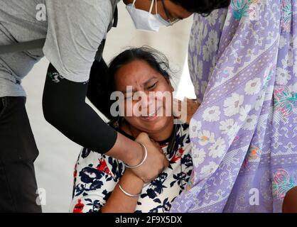 Una donna è consolata come lei piange dopo la morte del marito a causa della malattia del coronavirus (COVID-19) al di fuori di un ospedale COVID-19 ad Ahmedabad, India, 21 aprile 2021. REUTERS/Amit Dave
