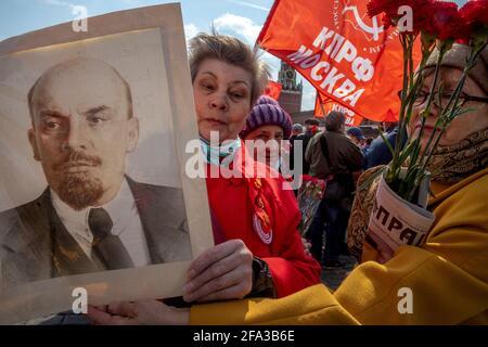 Mosca, Russia. 22 aprile 2021 UNA donna ha un ritratto del leader sovietico Vladimir Lenin mentre i sostenitori comunisti russi camminano per visitare il Mausoleo del fondatore sovietico Vladimir Lenin per celebrare il 151° anniversario della sua nascita, in Piazza Rossa nel centro di Mosca, Russia