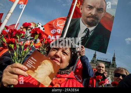 Mosca, Russia. 22 aprile 2021 i sostenitori comunisti russi camminano per visitare il Mausoleo del fondatore sovietico Vladimir Lenin per celebrare il 151° anniversario della sua nascita, in Piazza Rossa nel centro di Mosca, Russia. La bandiera recita 'Lenin - il creatore della primavera dell'umanità - URSS'