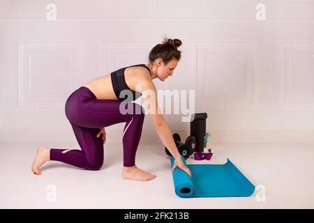 Attraente giovane donna pieghevole blu yoga o tappetino fitness per allenarsi. Forza e motivazione, sport e stile di vita sano, tenere in forma cepts. Female