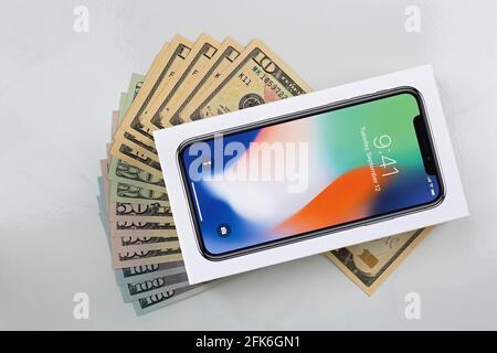 BANGKOK, THAILANDIA - GENNAIO 2018 : scatola di nuovo iPhone X (iPhone 10) su banconote americane su sfondo marmoreo il 17 gennaio 2018 a Bangkok, Tha