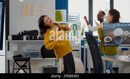 Felici diverse donne d'affari che ballano in ufficio aziendale celebrando il successo del progetto, cantando e divertendosi durante l'orario di lavoro. Ha entusiasmato gli ingegneri multietnici utilizzando un computer che mostra il software cad Foto Stock
