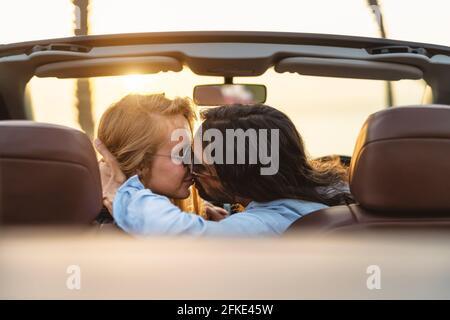 Felice coppia baciando in auto convertibile - persone romantiche che hanno momento tenero durante il viaggio su strada in città tropicale