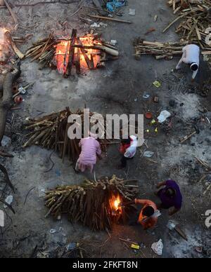 Nuova Delhi, India. 01 Maggio 2021. I lavoratori e i membri della famiglia portano un corpo per la cremazione vicino a più pire funerarie delle vittime di COVID-19 bruciare su un terreno che è stato convertito in un crematorio per la cremazione di massa a Nuova Delhi, India il Sabato, 1 maggio 2021. Foto di Abhishek/UPI Credit: UPI/Alamy Live News