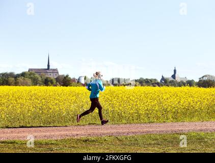 Estate con campi di colza fuori Vadstena, exerciser con il castello e la chiesa abbaziale di Vadstena sullo sfondo.
