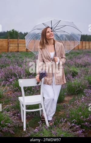 donna cammina in campi fioriti di lavanda con ombrello e gode di riposo. profondità di campo poco profonda foto